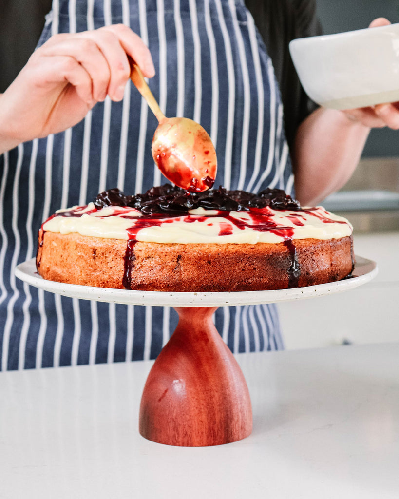 Lise Walsh decorating her tea cake with vanilla cream icing and cherry syrup on her Winterwares handmade cake stand