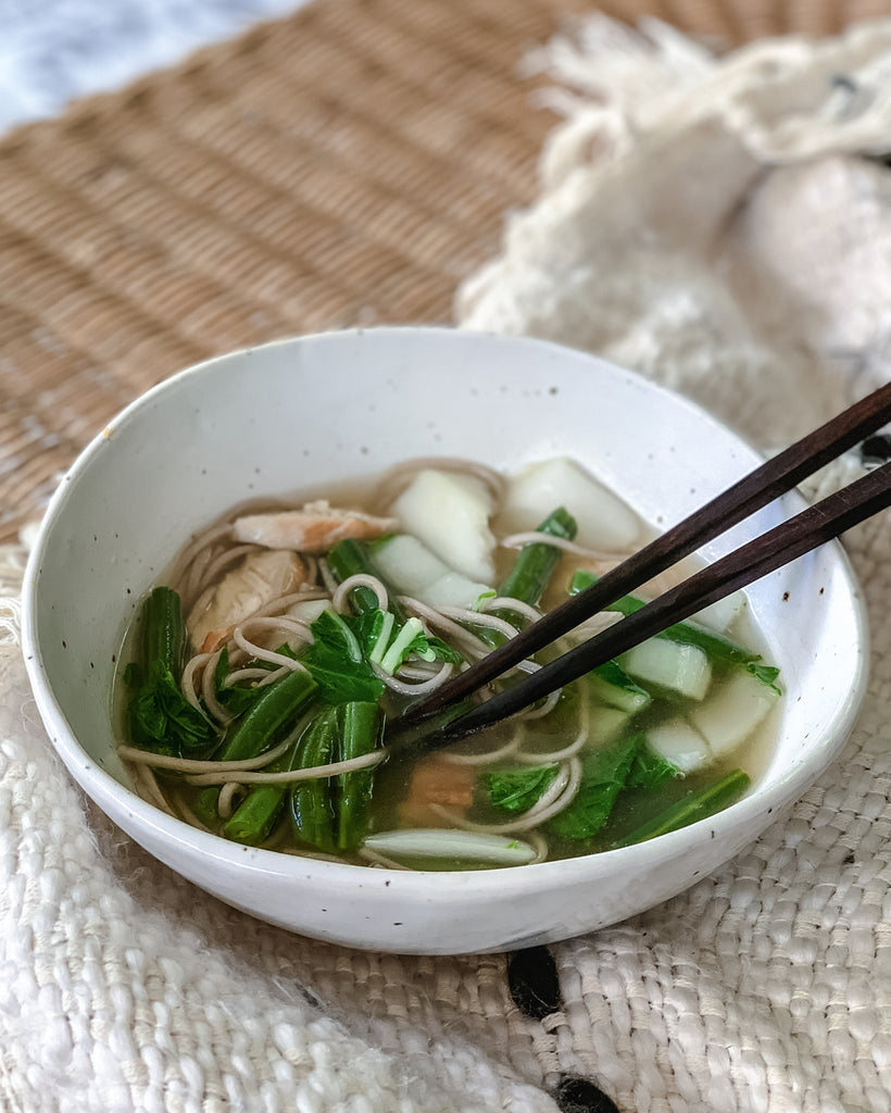 Chicken and soba noodle soup in a handmade ceramic bowl with bok choy