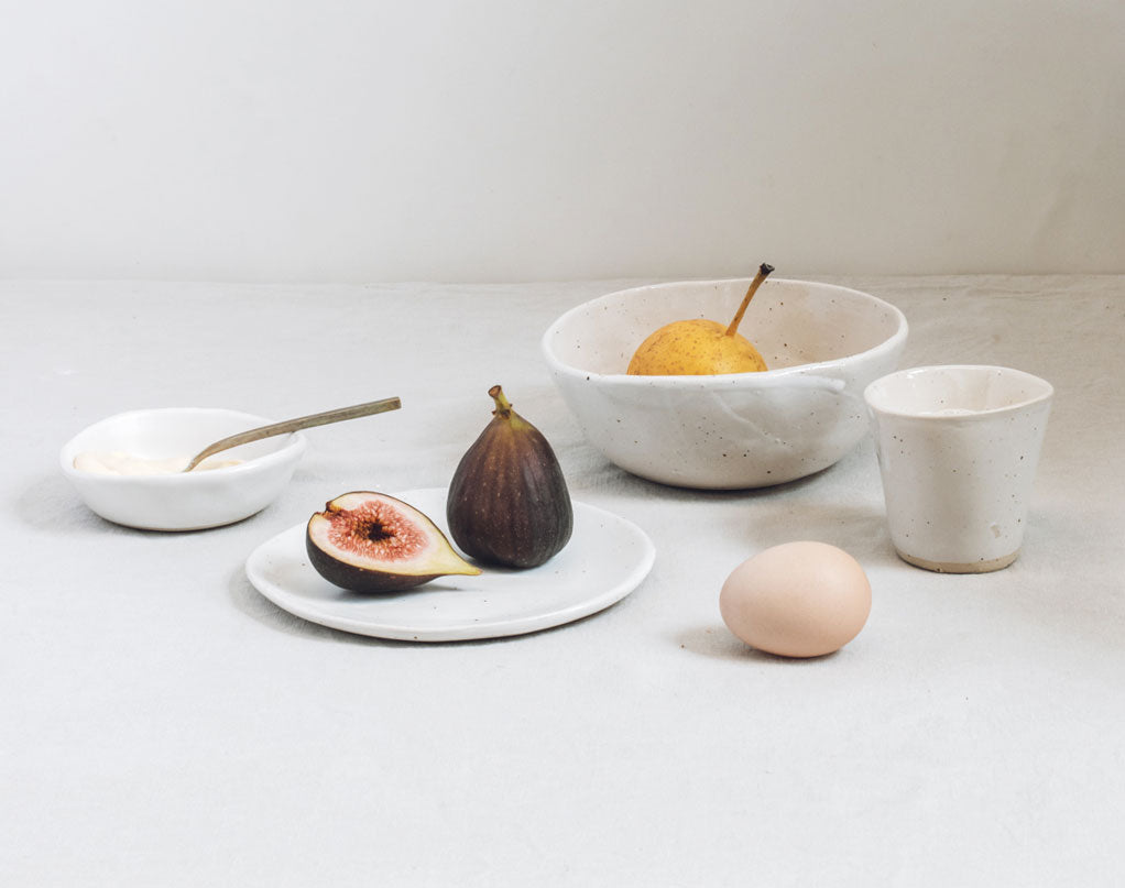 minimalist scene of winterwares handmade ceramic breakfast set, with two bowls, a plate and an espresso cup