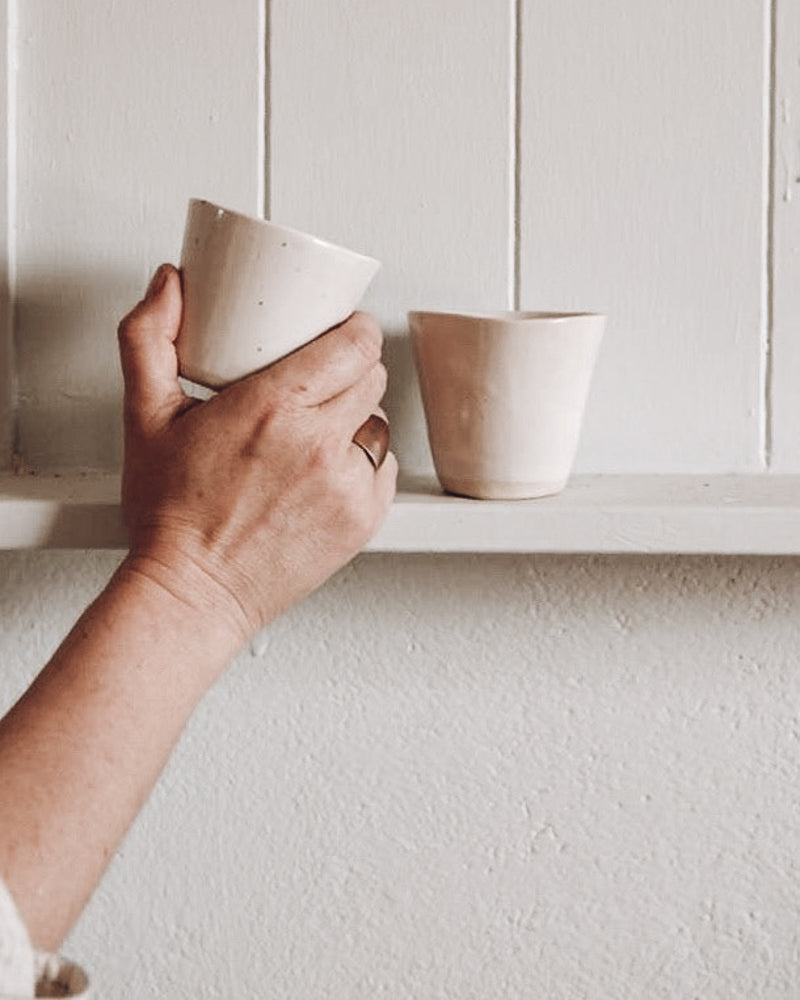 Stacking a pair of handmade ceramic tumblers on the shelf