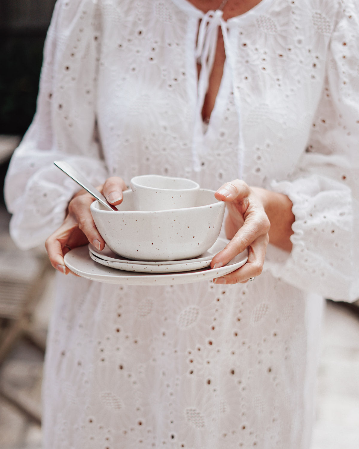 Holding a stack of handmade ceramic plates and bowls