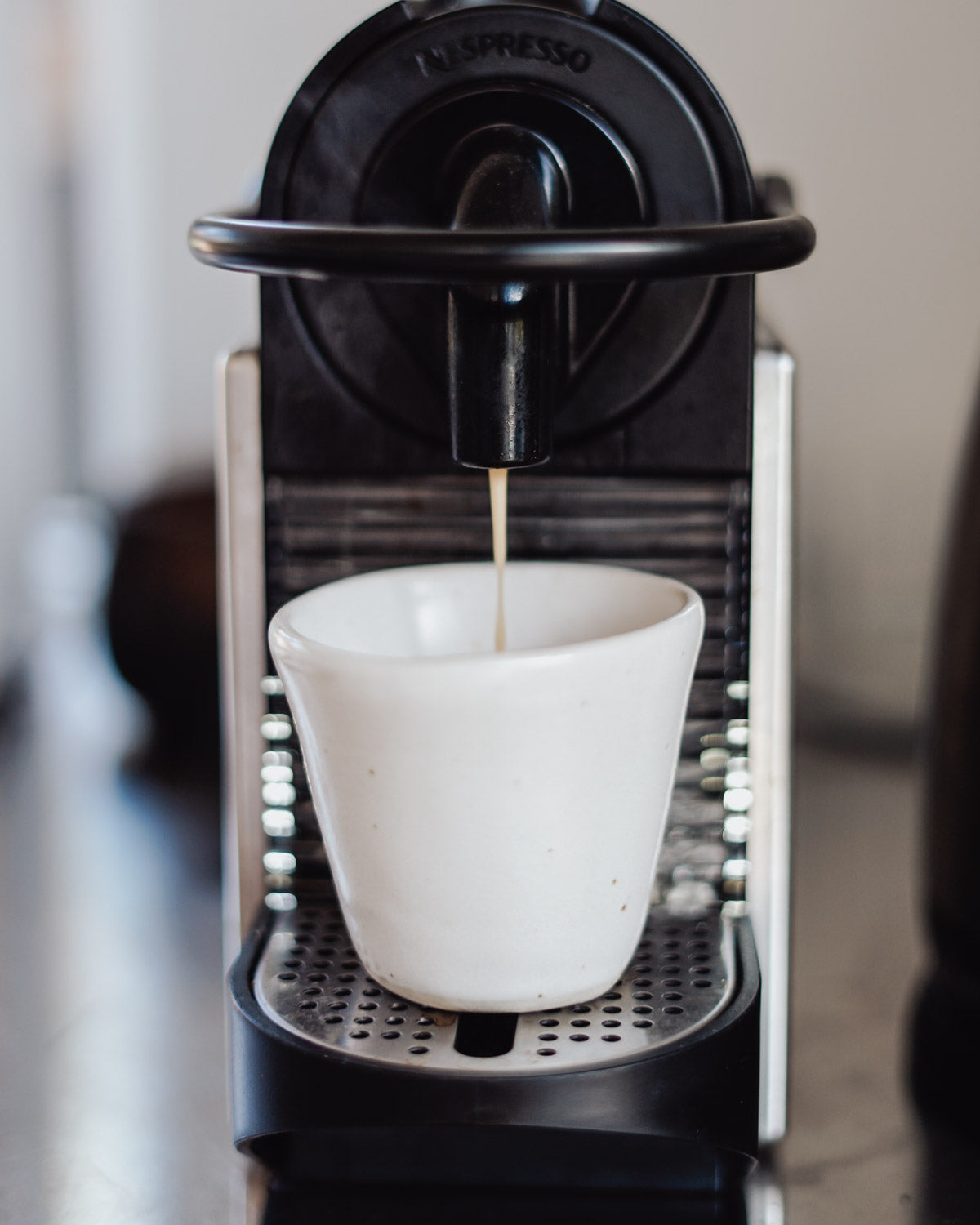 Handmade tumbler being filled with coffee in an espresso machine