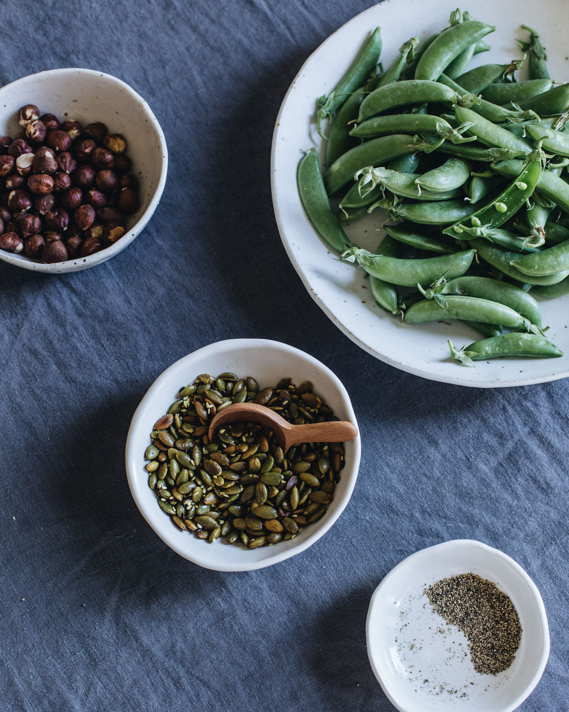 Little handmade bowls with pepitas, hazelnuts and pepper