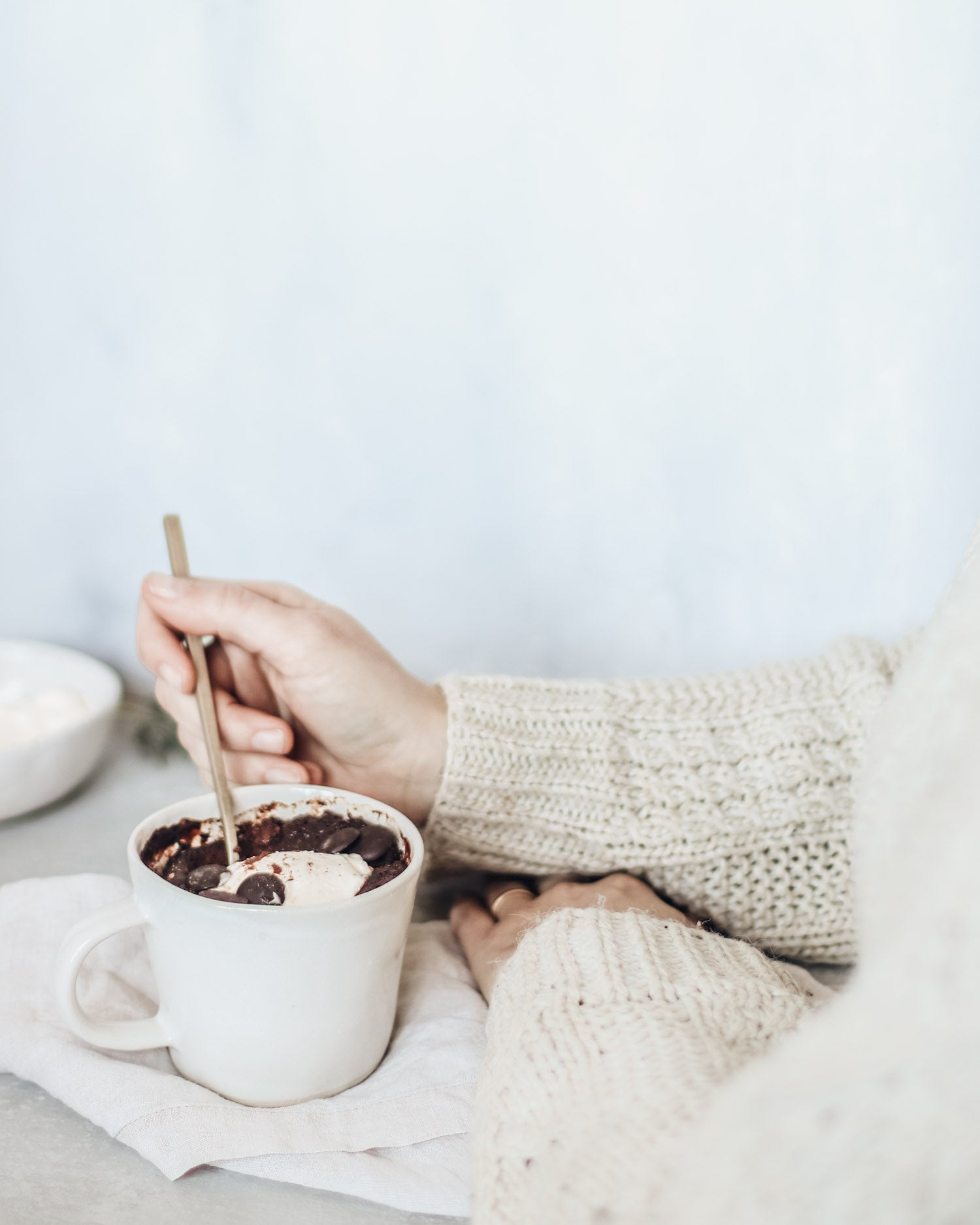 Baked chocolate pudding in a mug being enjoyed topped with cream
