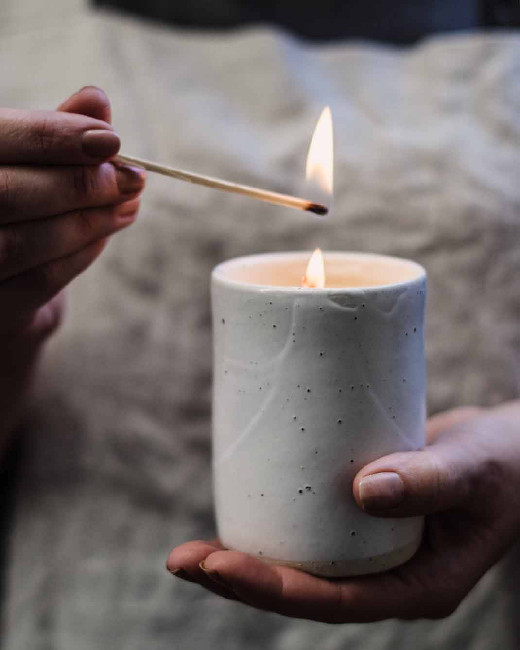 Hand cradling Winterwares Woodland Trail candle whilst being lit with match