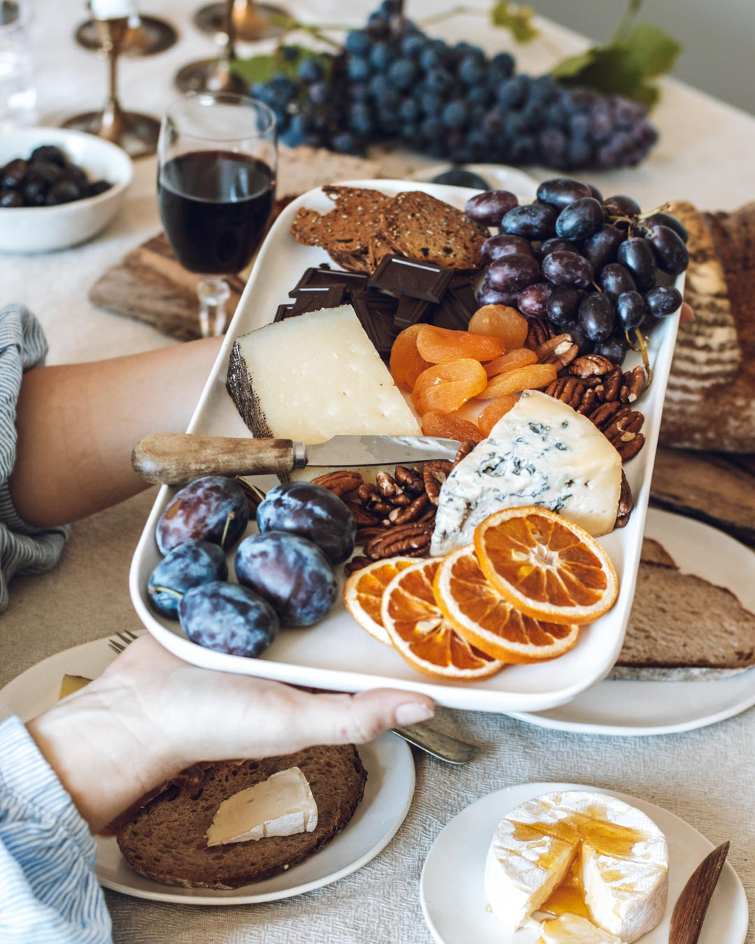 Passing a handmade ceramic platter laden with nuts, fruits and cheese across the table
