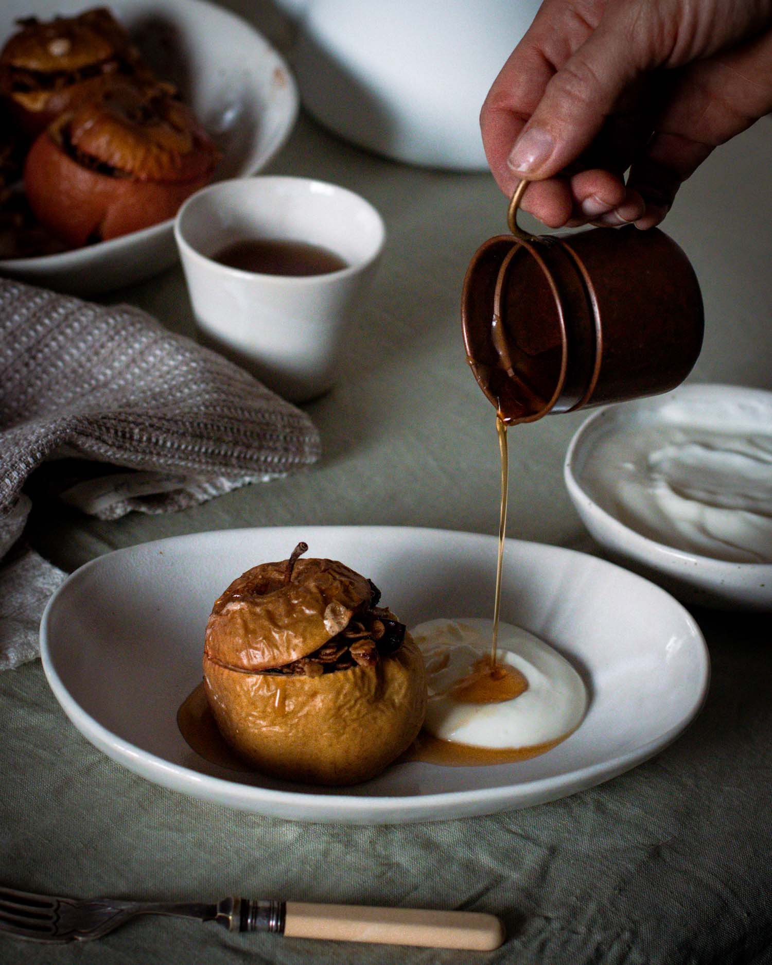 Pouring maple syrup over baked apples in a handmade ceramic bowl