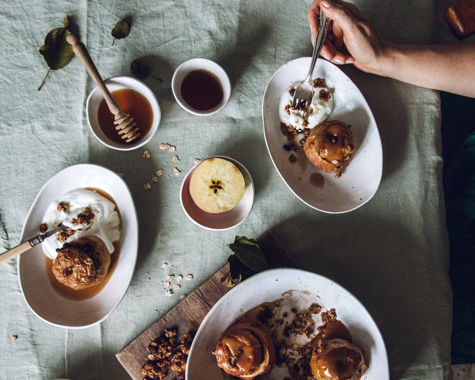 Table set with baked apples, syrup, yoghurt and tea.