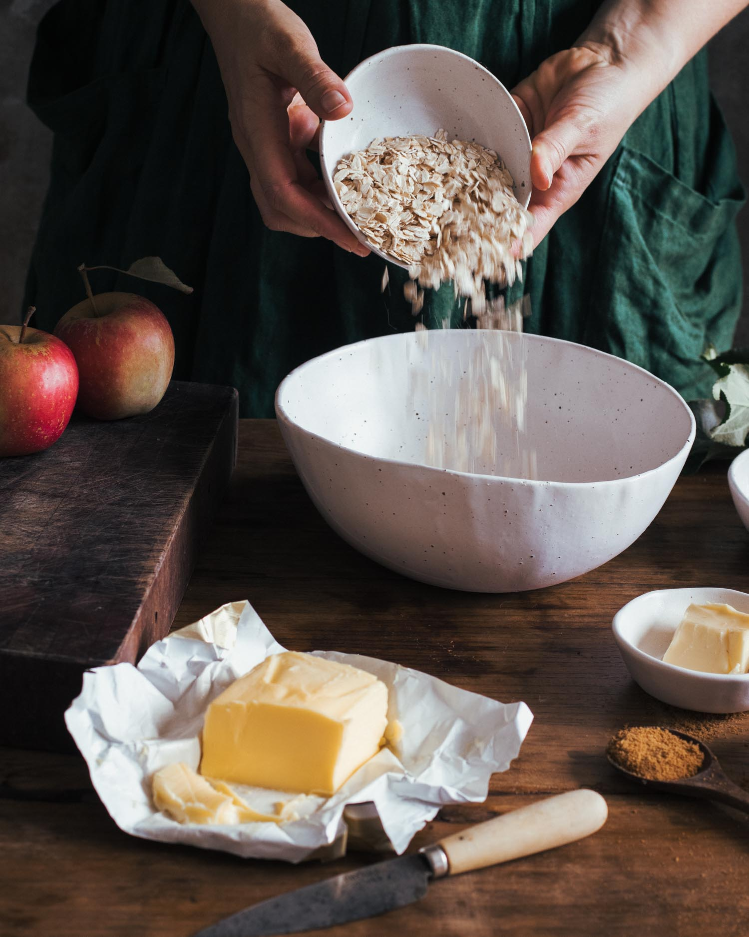 Pouring oats into a handmade ceramic mixing bowl
