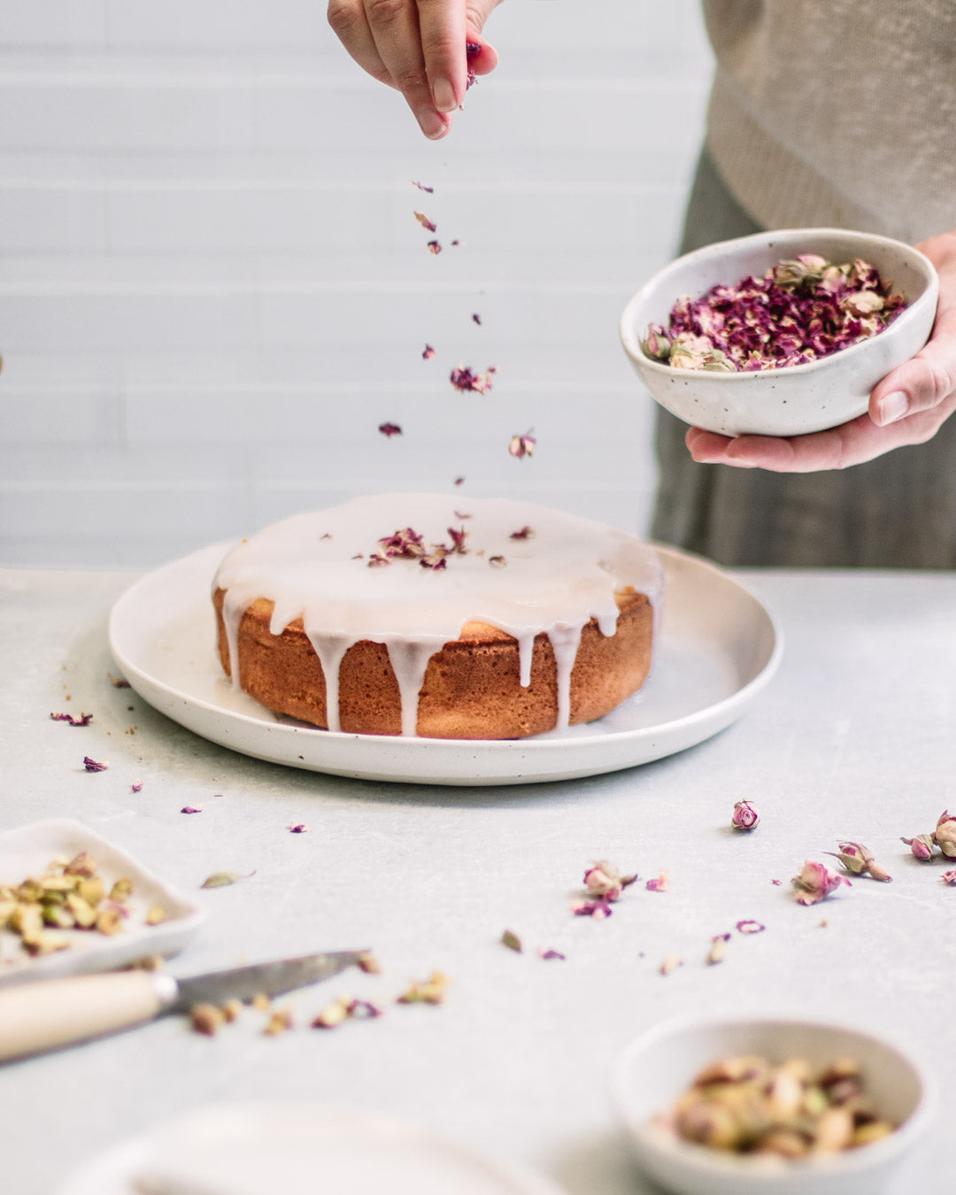 Persian Love Cake decorated with lemon icing, rose petals and pistachios