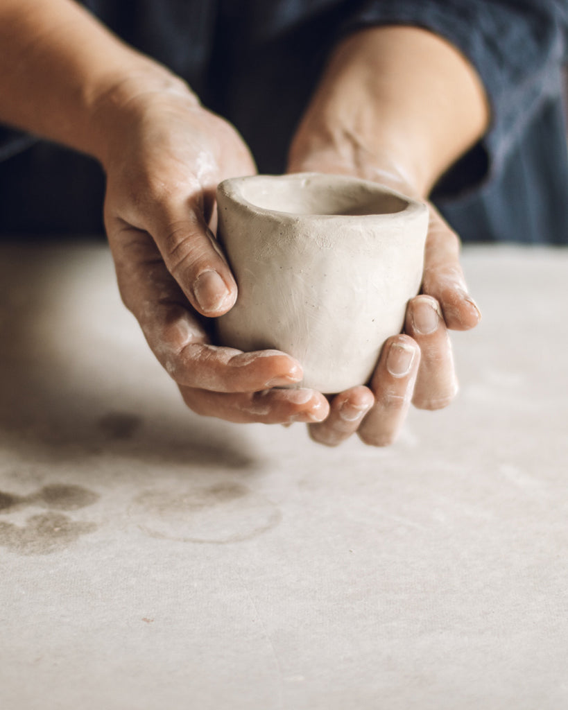 holding a handmade pottery cup