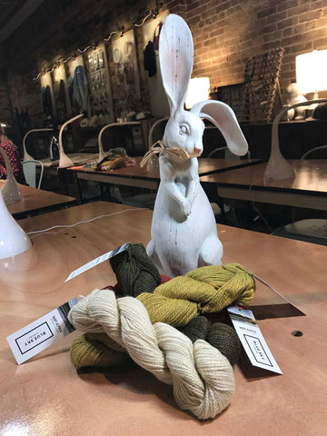Sculpture rabbit on table with array of yarns at his feet.