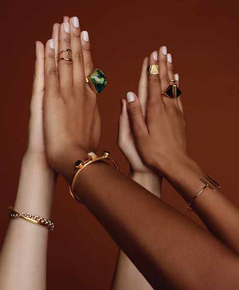 Two pairs of hands are stuck together--but beautiful, ethically-produced rings and bracelets are visible.