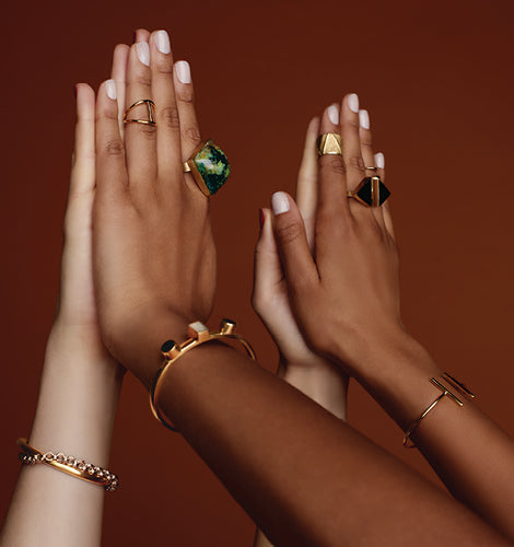 Two pairs of hands touching--beautiful, ethically-produced rings and bracelets are visible.