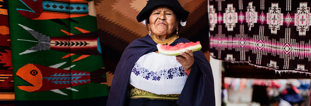 A woman finishes a slice of watermelon