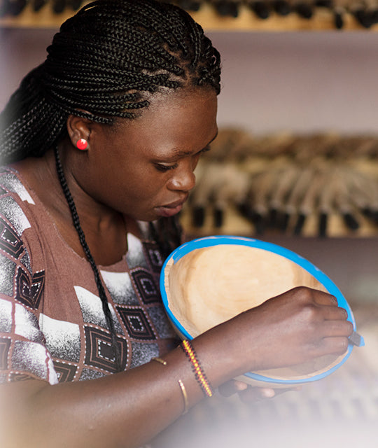 An artisan from Kenya puts the finishing touches on a painted bowl