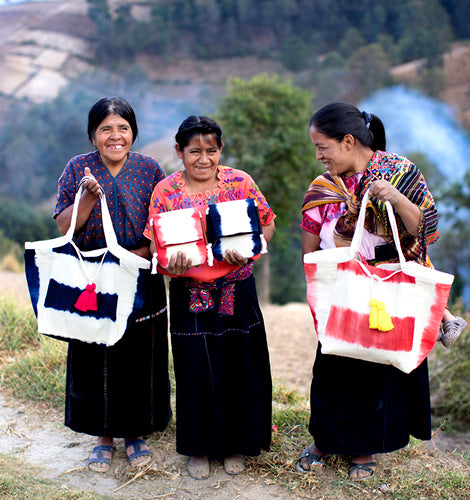 Giggling artisans hold their wares atop a remote mountain.