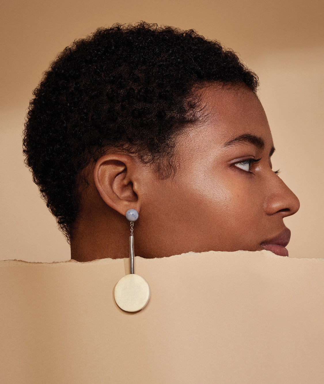 A model in profile dangles a single round earring over the rough edge of a ripped sheet of paper.