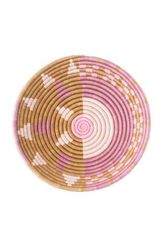 Split Plateau Basket by Indego Africa. Handwoven in Rwanda. This signature sweetgrass basket is handwoven with heart by artisans in Rwanda. Practicing a time-honored Rwandan weaving technique, the artisans use a needle and thread to wrap hand-dyed strands of sisal around bunches of sweetgrass to create tightly coiled, durable baskets. Color pink. 100% sisal.