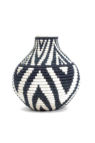 Black Mbao Vase by All Across Africa. Handwoven in Rwanda. Intricately crafted with timeless tradition, this carefully dyed sisal fiber and sweet grass vase makes a stunning statement piece. Color Black and White. 100% sisal.