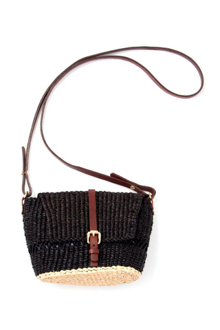 AAKS Spring 2018 Bika Shoulder Bag in Black. Hand woven raffia crossbody bag. Tonal adjustable and detachable leather strap with buckle closure. Linen lining with one inner pocket and drawstring closure. Measures 5 inches by 8 inches. 40 inch maximum strap drop. Color Noir. 100% raffia exterior. 100% linen interior. One Size.