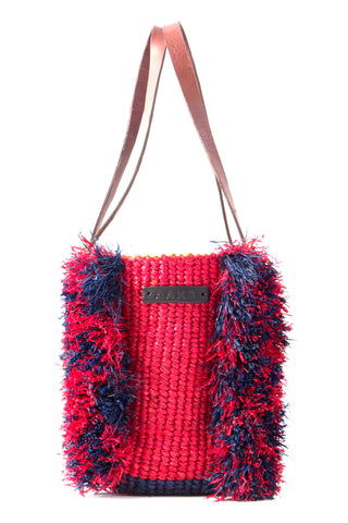 AAKS Spring 2018 Como Ruffle Tote. Hand woven raffia double handle tote bag. The Como Ruffle bag is rendered in 100% raffia with contrasting colours. The double handle offer up a modern spin on a classic style. One inner pocket. Drawstring closure. Measures 8 inches by 9.5 inches. 27 inch strap drop. Color red and blue. Woven raffia and 100% leather detailing. 100% cotton lining. One size.