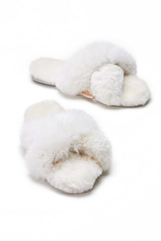 Ariana Bohling Criss Cross Alpaca Slide in White. Handmade in Peru from ethically sourced baby alpaca fur, these criss-cross style slippers come in crisp white and feature a comfortable half inch cushioned footbed for extra comfort. Slip on style. Open toe. Micro suede soles. Ethically handmade in Peru. Color white. 100% baby alpaca. Sizes Small Medium Large.