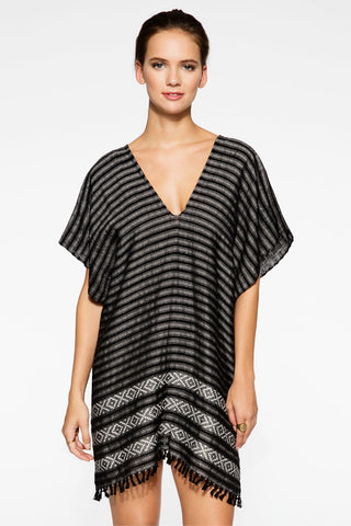 Wax and Cruz XO Caftan in Black and White. The XO Caftan is handwoven by master artisans in Mexico. It is an easy piece to throw on over your swim suit at the beach or wear over jeans with sandals. V-neckline with dolman sleeves and side slit at hem. Hand knotted fringe along hem. Measures 34 inches from shoulder to hem. Color black and white. 100% cotton. One size.