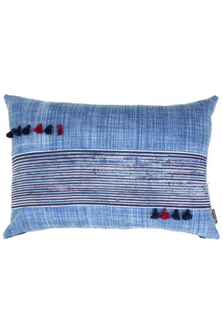 Sand Wash Tassel Lumbar Cushion by Anhad Craft. Handmade in India. Crafted from hand-dyed fabric, brushed to achieve a unique texture. Featuring hand stitched denim stripes made from upcycled denim, and contrast pom poms for a fun added flare. Color blue. Made from upcycled denim.