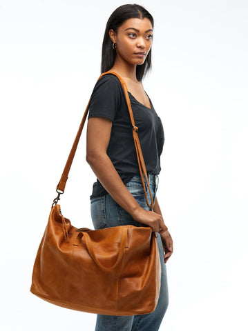 ABLE Spring 2018 Alem Leather Weekender in Cognac. Featuring a lined interior, exterior pocket for your phone, passport, or boarding pass, two interior pockets, and a removable / adjustable crossbody strap. 1 exterior pocket, 1 interior zipper pocket, 1 interior slit pocket and a removable and adjustable crossbody strap with a strap pad for extra comfort. Measures 13 inches by 22 inches. 7.5 inch depth. Color brown. Handcrafted in Ethiopia. 100% leather with a cotton lining. One size.