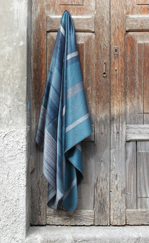 Calypso Throw by Shupaca. Handmade in Ecuador. These Alpaca throws are thin, lightweight yet extremely warm. Made from Peruvian Alpacas fibers, the throws are luxuriously soft, sleek and sophisticated. Color Blue. 80% alpaca, 20% acrylic.