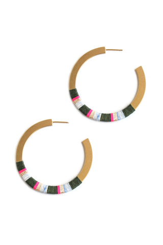 Bluma Project Spring 2018 Madison Hoop in Olive. Big bold hoop with vibrant thread striping. Perfect slice of color and shine. Cut plate hoop with wrapped thread stripes. Post fastening for pierced ears. 2 inch diameter. Color olive gold. Gold plated brass, linen and lurex thread. One size.