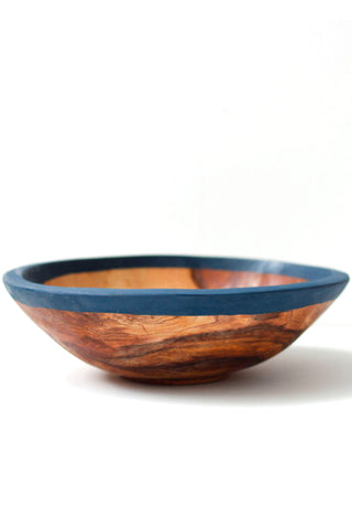 "Olive Wood Kuni Bowl from Badala. Bring a warm ambience to your kitchen with olive wood and a splash of color. This color blocked wood bowl is BADALA's take on a kitchen staple and works wonderfully as a serving bowl or decorative vessel. Handcrafted in Kenya from locally sourced olive wood. Measurements 9"" diameter (approximate)"