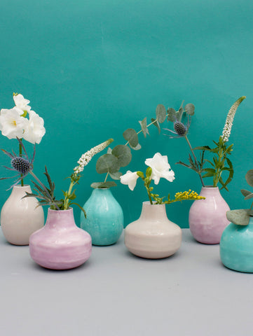 Enamel Bud Vase Trio handmade in India from enameled tin and painted soft pastel shades of cream, lilac or aqua to create a beautifully simple finish. A contemporary style in three different sizes, these small round vases are an ideal gift. Ethically Handmade in India Painted Enameled Iron Sold Individually. Height: 4 - 4.7in  / 10-12cm Diameter: 4.3 - 5in / 11-13cm