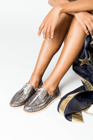 "Cano Clothing Fall 2018 Benito Huarache in Antimony. Lace up woven huarache shoe. Closed toe. Open weave. The elaborately woven structure is made out of the smoothest high quality vegetable-tanned leather to reduce the ""break-in"" phase. Each pair is handmade from start to finish by artisans in Mexico. Color silver. 100% vegetable tanned leather. Rubber sole. Sizes 37 38 39 40."