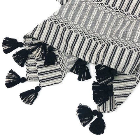 Volcanic Sands Throw by Del Palomar. Handmade in Guatemala. Handwoven authentic Guatemalan fabric throw, featuring an intricately woven textured pattern and adorned with black and white tassels. Handwoven on a traditional footloom by local artisans in Chimaltenango, Guatemala. Color black and white. 100% cotton.
