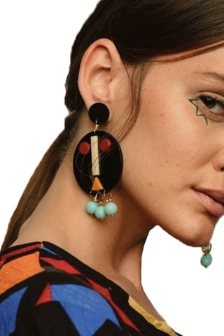 Disco Rojo The Face Earring in Black. Inspired by the illustrated faces of Italian artist Bruno Munari, The Face earring adds an unexpected excitement to any outfit. Post earring. Handmade in Colombia. Designed in Barcelona. Color black teal red yellow white. Acrylic, natural stones, silver fastenings. One size.