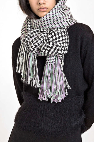 Escudo Fall 2018 Sparrow Scarf. Large wrap scarf in black and white houndstooth pattern. Handwoven with pale purple and green accents. Reversible with long fringe tassels. Color black white green purple. 100% Baby Alpaca. One size.