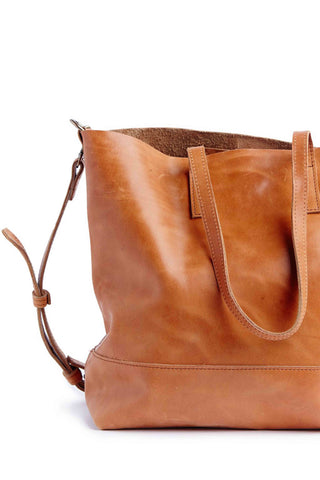 Abera Cross body Leather Tote can be worn over the shoulder or across your body and is the ideal size to function as your work bag or as your everyday purse //  Hand-crafted in Mexico + Ethiopia from 100% Ethiopian leather. Features shoulder straps, adjustable cross body strap, interior pocket and magnetic closure. 12.5'' H x  16.5″ W x  5.5″ D