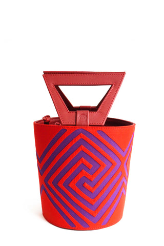 Nabba Tote by Fe Handbags. Handmade in Colombia. Nabba Bag featuring a bright denim Mola made by indigenous people from the Gunadule Tribe. Polished gunmetal gold plated metal fastenings. Detachable leather strap for alternative styling. Color red. 100% calfskin leather.