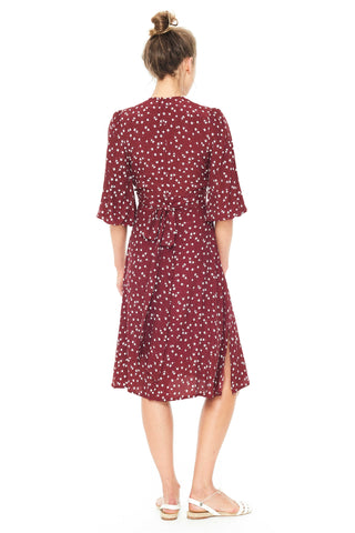 Faithfull Resort 2018 Chloe Midi Dress in Berry Betina Floral Print. Midi length dress deep-V neckline and front button detail in Faithfull's Berry Betina Floral print. Flutter sleeves and hidden zipper at back. Fitted at waist with back bow tie. Color red burgundy. 100% Rayon Crepe. Sizes x-small small medium large.
