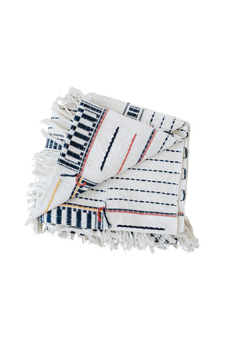 Adjoukrou Blanc Throw by Five Six Textiles. Handwoven in Côte d'Ivoire. The intricate Adjoukrou motif is a Five | Six staple. Mixing bold motifs with airy lines, this blanket is perfect on your favorite reading chair or as your go-to travel blanket. Color multi. 100% raw cotton.