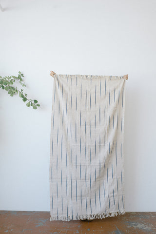 Nori Siri Throw by Five Six Textiles. Handwoven in Côte d'Ivoire. A blend of white and brown threads interwoven with sparks of bright blue Siri Siri detail. Handwoven on handmade upright frame wooden looms using the same techniques that have been used for hundreds of years. Color natural blue. 100% raw cotton.