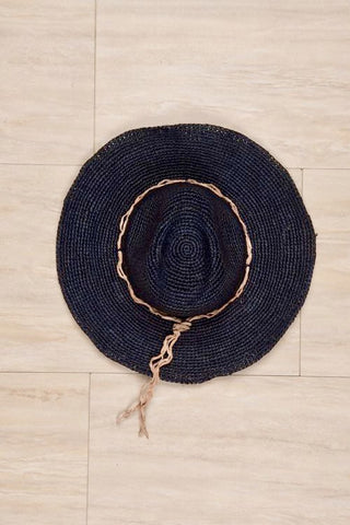 "Mar y Sol Mika Hat in Navy. Medium brim fedora crocheted raffia sun hat with adjustable wire brim. Handmade in Madagascar. 4"" brim, 5"" crown, 23"" circumference. Color navy. Crafted using organically tanned leathers and responsibly sourced raw materials. 100% crocheted raffia with organic leather trim and interior cotton sweatband. One Size Fits Most."