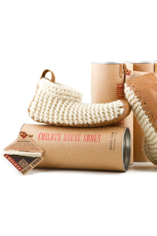 House shoes by Chilote. Handmade in Chile. Slippers 100% hand made by artisan women in Patagonia using only natural sheep wool and up-cycled salmon leather. With use, they will conform to the shape of the wearer's own foot. Color white. 100% wool.