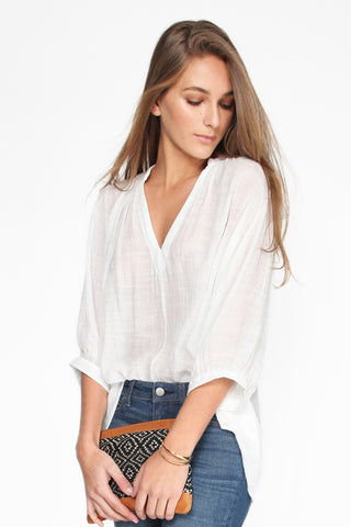 Accompany Exclusive Sitting Pretty Asmara Top in Ivory. Loose oversized blouse with gathered split V-neckline, three quarter sleeve, gathering at back panel, dipped curved back hem. Pull over style. Measures 24 inches from shoulder to hem. Color white. 100% ghost chiffon. Sizes Small Medium Large.