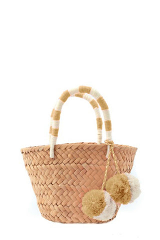 Kayu St. Tropez Tote in Natural. Woven tote bag made of natural seagrass featuring matching raffia poms poms. Roomy enough for your beach towel, sunglasses and more. Featuring playful pom-poms and an embroidered handle. Double yarn wrapped handles. Open top. Unlined. 4.5 inch handle. Color natural white. Made from all-natural woven seagrass and raffia. Sizes Mini Medium.