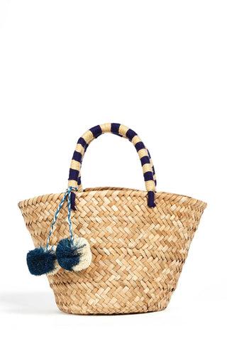 Kayu St. Tropez Tote in Navy and Natural. Woven tote bag made of natural seagrass featuring matching raffia poms poms. Roomy enough for your beach towel, sunglasses and more. Featuring playful pom-poms and an embroidered handle. Double yarn wrapped handles. Open top. Unlined. 4.5 inch handle. Color natural blue white. Made from all-natural woven seagrass and raffia. Size Mini.