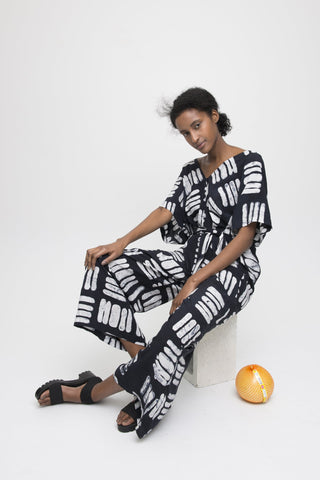 Osei-Duro Spring 2018 Easy Jumpsuit in Black Basket. Loose fitting jumpsuit with self-tie, removable belt. Dolman sleeves and deep V at front and back neck. 21.5 inch inseam. Color hand dyed batik black print. 100% Rayon. Sizes X-Small Small Medium Large.