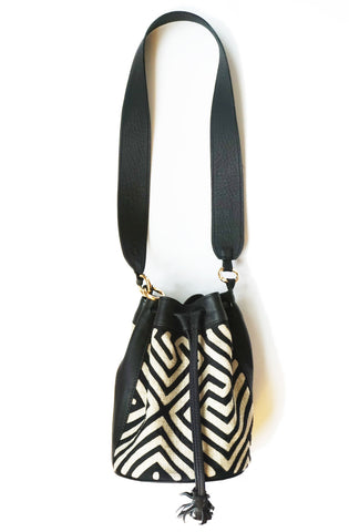 Tule Shoulder Bag by Fe Handbags. Handmade in Colombia. Mochila Tule Bag featuring a denim Mola made by indigenous people from the Gunadule Tribe. Polished gunmetal gold plated metal fastenings. Detachable leather strap. Color black and white. Genuine leather.
